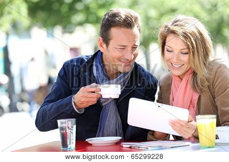 Couple at coffee shop websurfing with tablet