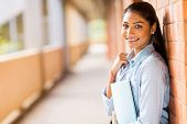 happy indian college student leaning against wall poster