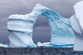 Huge Arch Shaped Iceberg in Antarctic waters with a boat in the distance poster