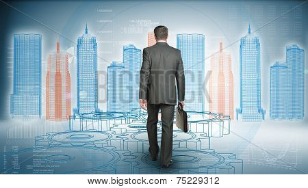 Businessman in suit holding briefcase and goes forward. Rear view. Wire-frame glowing building on ba