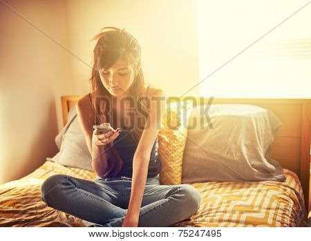 tech savvy asian teen girl using smart phone in bed room