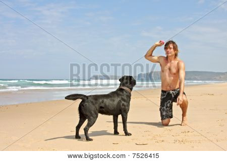 Young guy playing with his dog at the beach poster