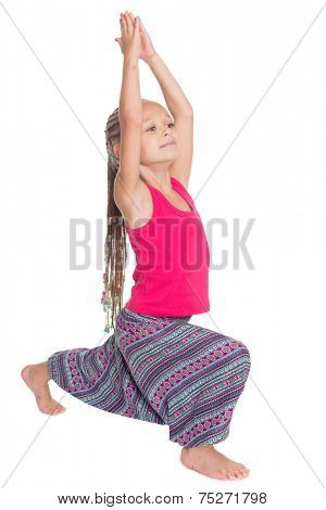 Little girl doing exercises of yoga in Asian attire. Girl is six years old