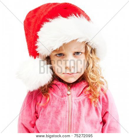 Sad girl in santa hat. Child isolated on white