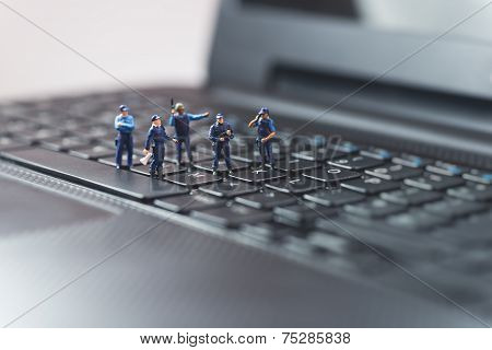 Miniature Police Squad Protecting Laptop Computer. Technology Concept