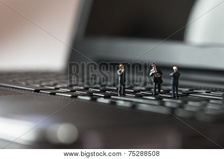 Miniature Business People Standing On Laptop Keyboard