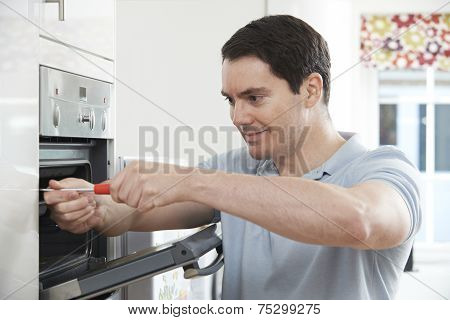 Repairman Fixing Domestic Oven In Kitchen