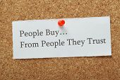 The phrase People Buy From People They Trust on a cork notice board as a concept for businesses to build customer trust and loyalty to their product or service. poster