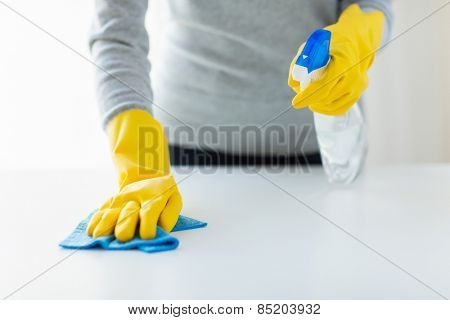 people, housework and housekeeping concept - close up of woman hands cleaning table with cloth and detergent spray at home