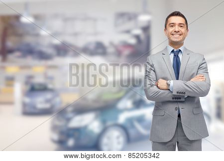 business, car sale, consumerism and people concept - happy man over auto show or salon background