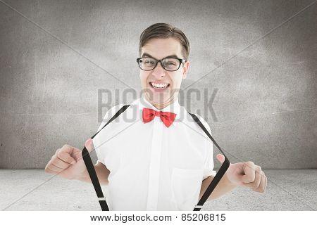 Geeky hipster pulling his suspenders against grey room
