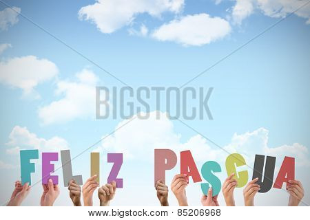 Hands holding up feliz pasqua against blue sky