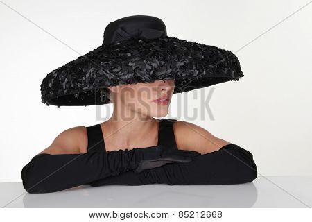 Close up Mysterious Woman Wearing Elegant Black Feathery Hat and Long Gloves Leaning on the Table, Isolated on White Table.