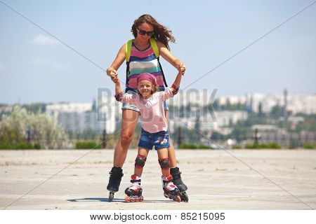 Young mother with her 5 years old daughter rollerskating in park