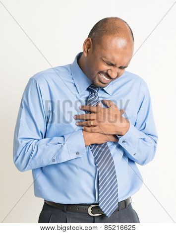 Indian businessman heartache, pressing on chest with painful expression, on plain background