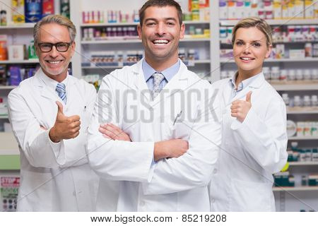 Team of pharmacists smiling at camera at the pharmacy poster