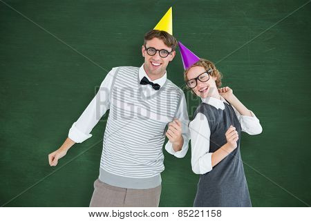 Geeky hipster couple wearing a party hat against green chalkboard