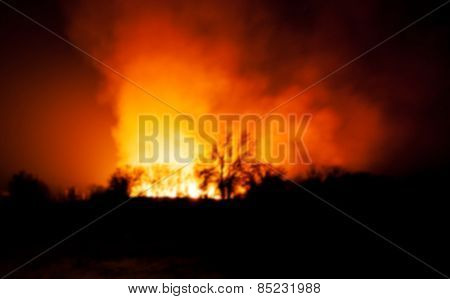 Blurred background image of an approaching wildfire at night, dramatic colors and sense of lingering danger