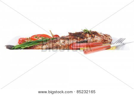 main course isolated on white: whole fried sunfish on plate with lemons and peppers
