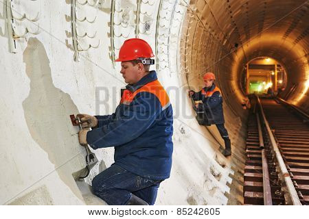 Tunneller worker installing fixture in underground subway metro construction site