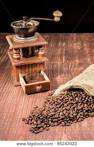 Coffee beans ly spilled from a hessian bag on a wooden table with an old grinder in the back. poster