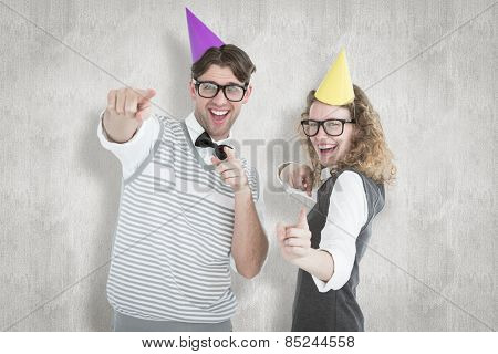 Happy geeky hispser couple dancing with party hat against white background
