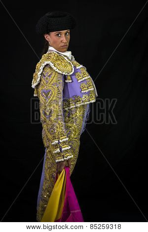 Woman bullfighter holding capote pink
