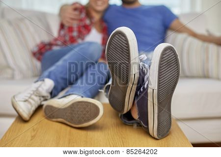 moving, home, repair and people concept - close up of couple legs relaxing and sitting on sofa with legs on table in new apartment