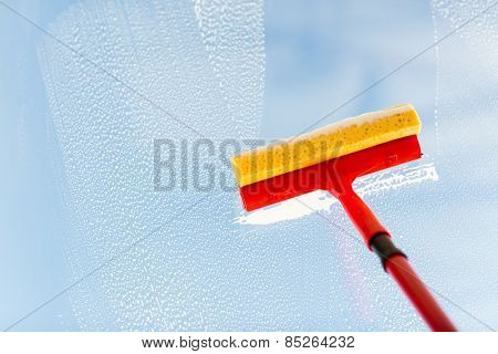 people, housework and housekeeping concept -close up of hand cleaning window glass with sponge mop and foam