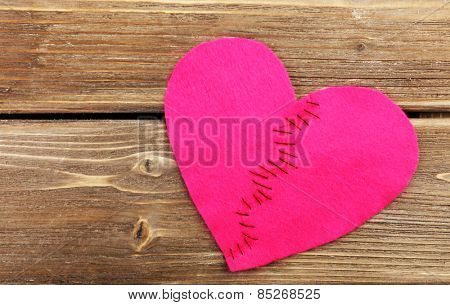 Broken heart stitched from two pieces on wooden background