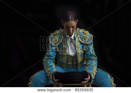 Woman Bullfighter Sitting On A Chair Looking At His Montera Concentrated