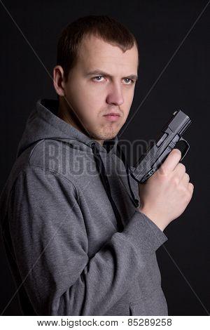 Young Man Criminal Holding Gun Over Grey