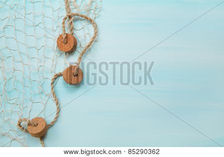 Maritime nautical blue and turquoise wooden background with a fishing net.