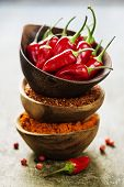 Red Hot Chili Peppers with herbs and spices over wooden background - cooking or spicy food concept poster