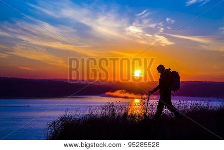 Walking female hiker silhouette and impressive colorful sunrise on the background