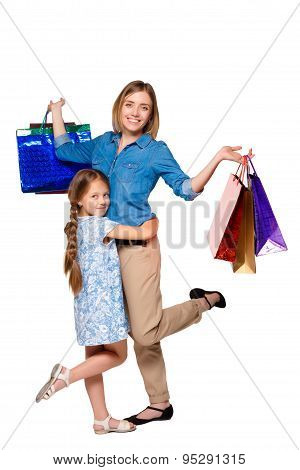 Happy a mother and daughter with shopping bags standing at studio
