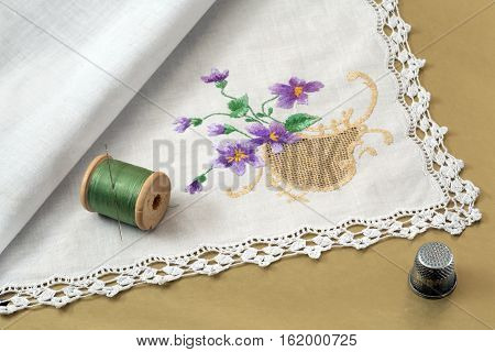 handkerchief thread needle and thimble on a gold background