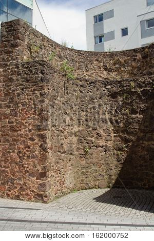 The proximity of the modern architecture and the remains of an ancient Roman wall in the city center of Exeter.