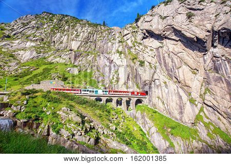 Train On The Railway Bridge Teufelsbrucke Over Reuss River In St. Gotthard Mountain Range Of Swiss A