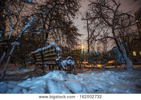 bench and trees in the snow in the light of night lanterns on a background of high-rise buildings