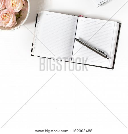 White desk with opened notebook. Top view, flat lay