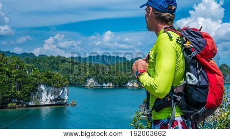 Traveler with Backpack enjoys the View over Roks in Kabui Bay near Waigeo. West Papuan, Raja Ampat. Indonesia