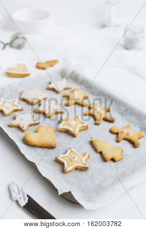Decorating Christmas Shortbread Biscuits on Baking Tray with Vanilla Icing and Silver Sugar Balls on White Table