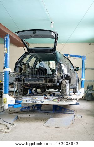 Moscow, Russia - December, 9, 2016: Black crashed car on stocks in a car repair station