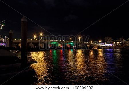 Colorful holiday lights on a boardwalk along the harbor at Balboa Island.