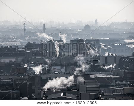 Smog - city air pollution. Unclear foggy atmosphere polluted by smoke rising from the chimneys in the urban city centre and silhouettes of rooftops, Budapest, Hungary