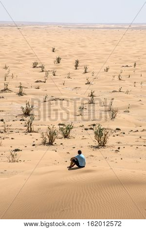 Man tourist in desert rub al khali in Oman sitting in sand view landscape 3