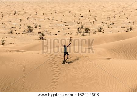 Man tourist in desert rub al khali in Oman throwing sand
