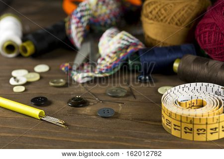 Sewing tools and measuring tape on a wooden background