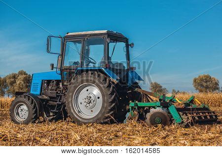 Autumn afternoon tractor rides and pulls the plow plow a field after harvest of cereals - corn. On the ground are dry stalks.